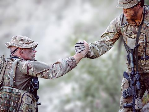 one soldier lends a hand to another